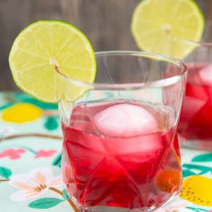 the woo woo cocktail, cranberry red drink in a clear glass garnished with lime
