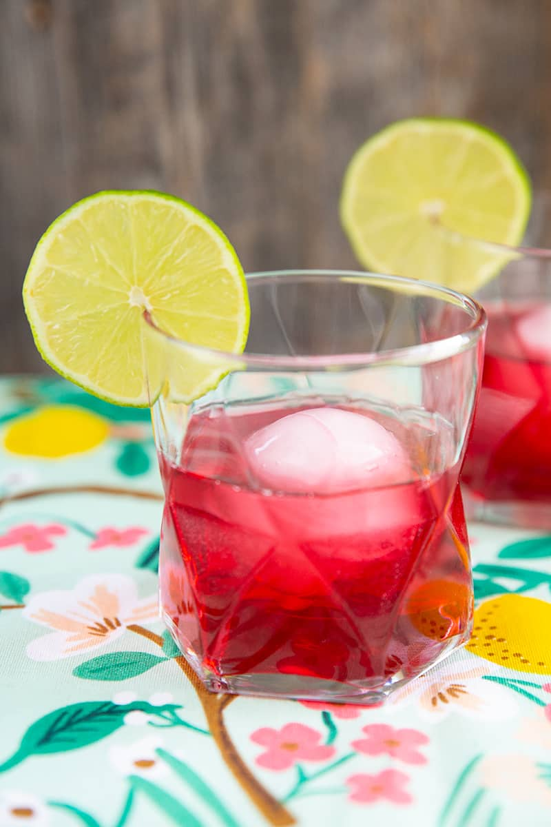 close up woo woo cocktail, cranberry red drink in clear glass garnished with lime