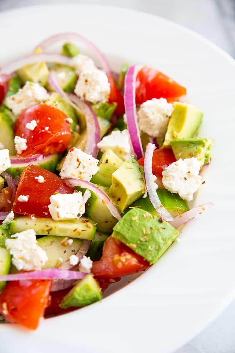 close up Greek avocado salad on a white bowl consists of sliced avocado, cucumber, tomatoes, lemon, feta, red onions and Greek seasoning