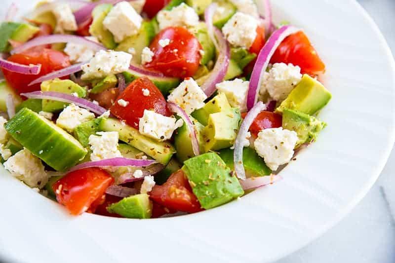 Greek avocado salad on a white bowl consists of sliced avocado, cucumber, tomatoes, lemon, feta, red onions and Greek seasoning