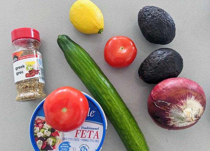 avocado salad ingredients consists of avocado, cucumber, tomatoes, lemon, feta, red onions and Greek seasoning