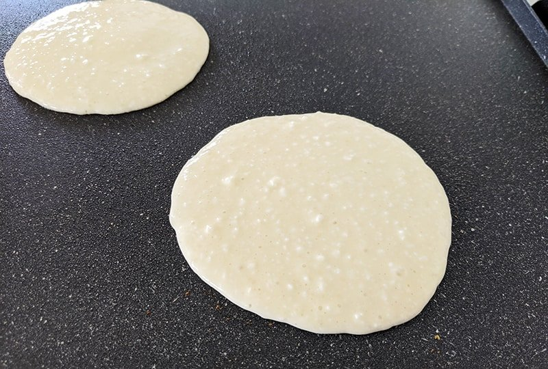 scooped cottage cheese pancake batters cooking on the griddle