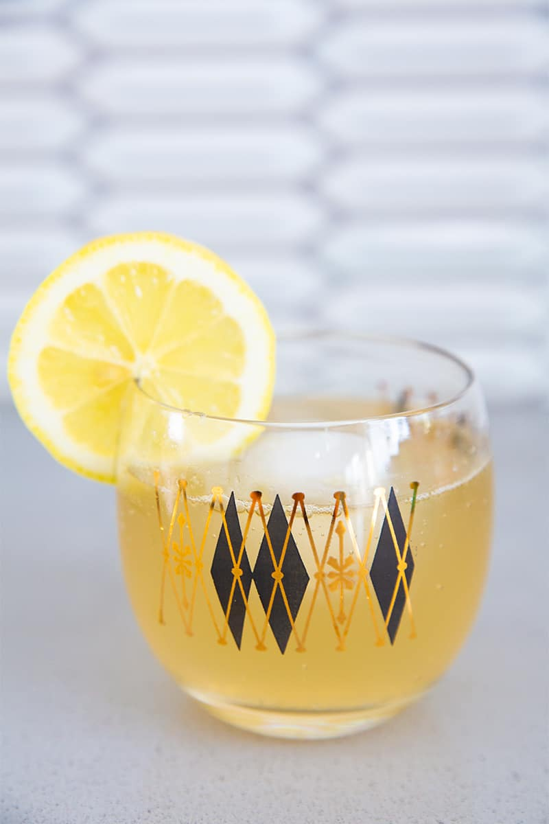 a gin buck cocktail in a roly poly glass with a lemon wedge garnish on the side