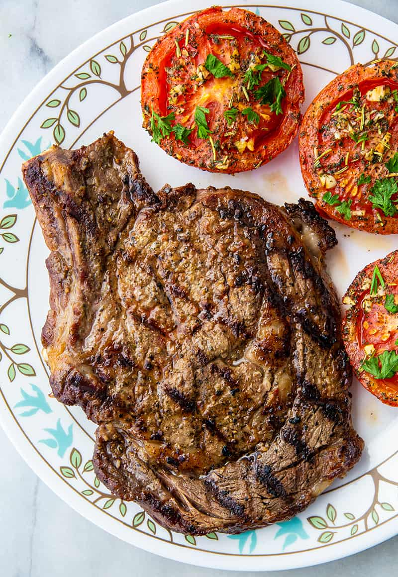 close up of grilled rib eye steak on a white plate with tomatoes