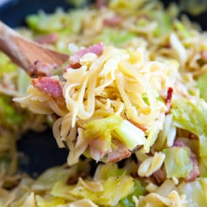 cabbage, onions and noodles with bacon on a wooden spoon