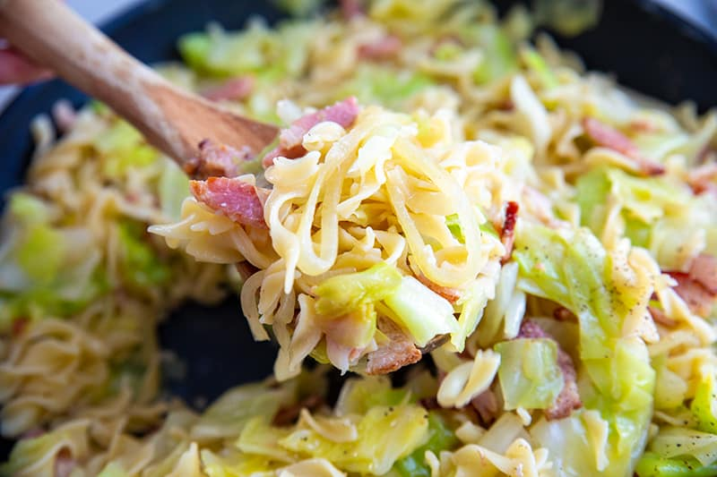 Fried cabbage, onion and noodles with wooden spoon