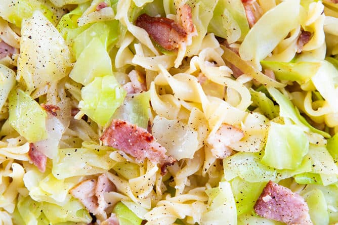 close up of cabbage, onions and noodles with bacon in a black frying pan