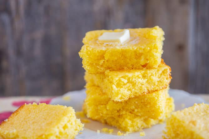 a stack of Jiffy cornbread slices with melting butter on top on a white plate