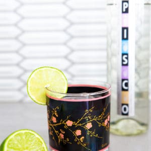 A bottle of pisco and a pisco sour garnished with a fresh lime in a vintage black and pink glass beside a fresh lime