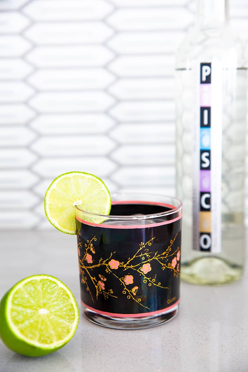 close up bottle of pisco and a pisco sour cocktail garnished with a fresh lime in a vintage black and pink glass beside a fresh lime