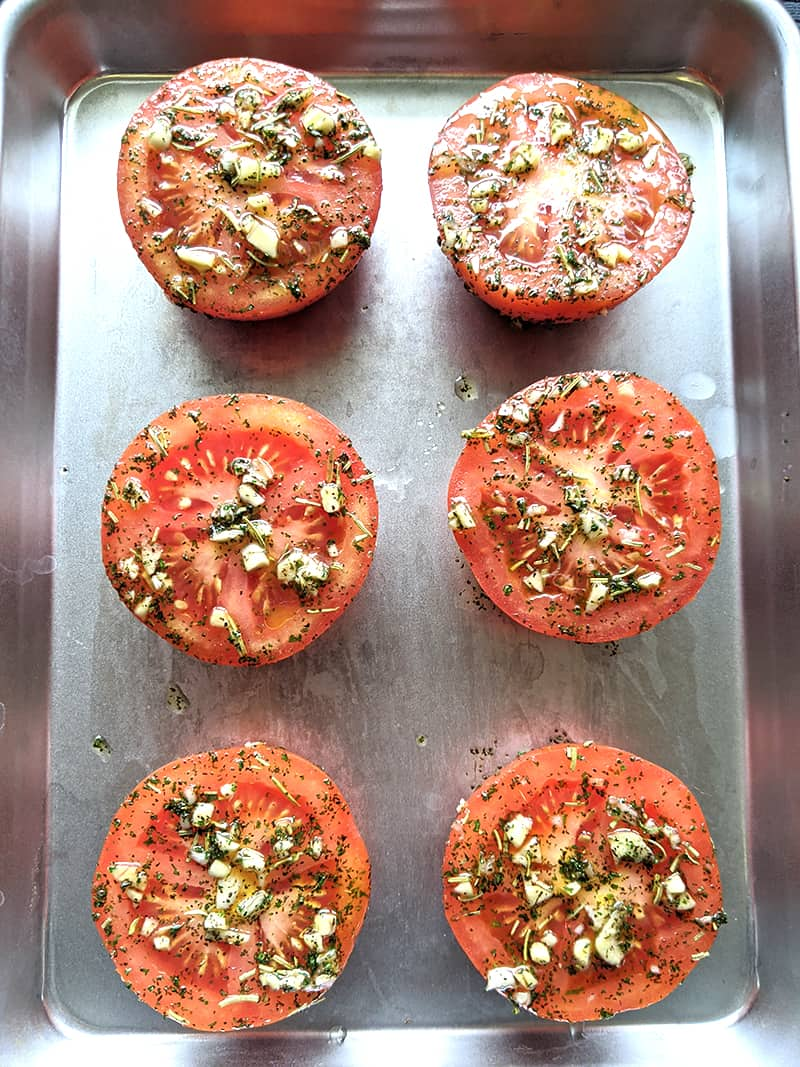close up of oven roasted tomatoes on a sheet pan loaded with garlic and herbs