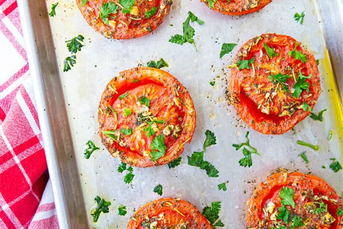 close up of oven roasted tomatoes on a sheet pan loaded with garlic and herbs on a red kitchen towel underneath