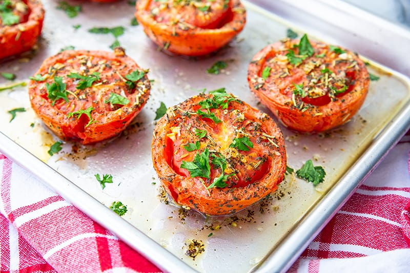 oven roasted tomatoes on a sheet pan loaded with garlic and herbs on a red kitchen towel underneath