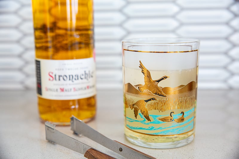 Scotch and Soda in a bird glass on a table with a scotch bottle in the background.