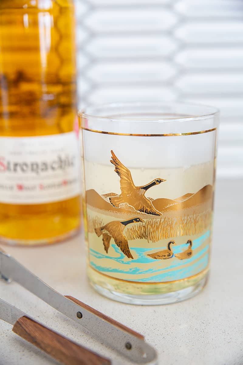 scotch bottle with ice tongs and a vintage Canada goose glass with scotch and soda in it
