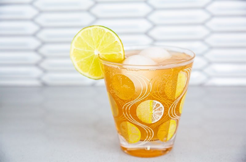 a suffering bastard cocktail in a stunning glass with gold emblazoned garnished with a lemon wedge on the side