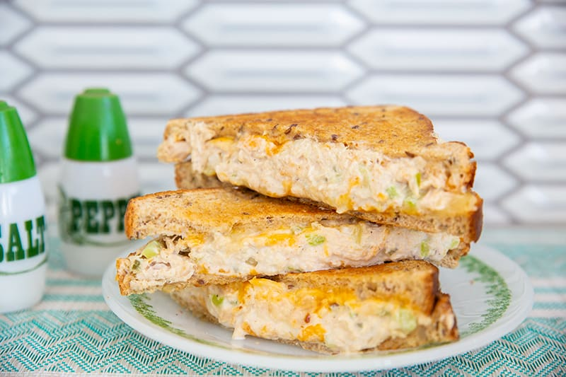 cheesy tuna melt sandwich pieces stacked on top of each other on a white plate with salt and pepper shakers at the side