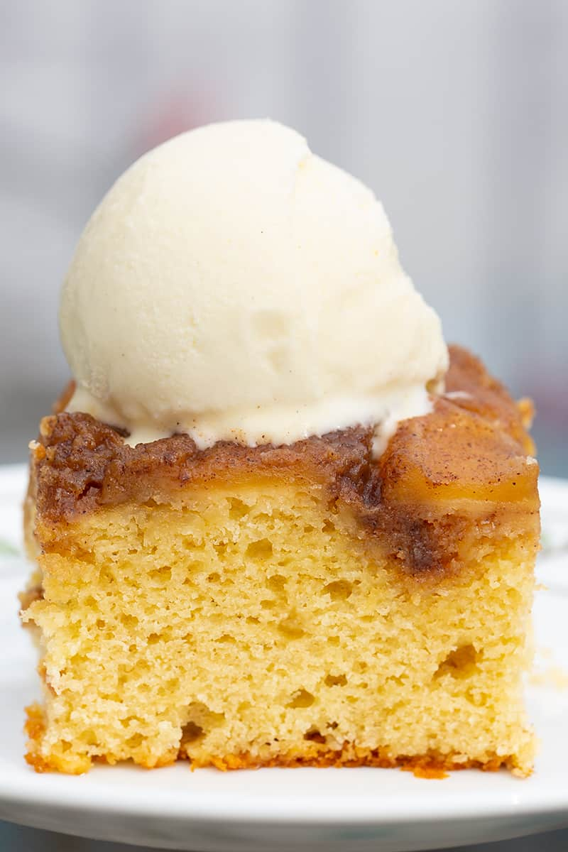 close up slice of upside down apple cake with cinnamon spice apple topping and vanilla ice cream