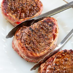 three pieces filet mignon wrapped in bacon on a white plate