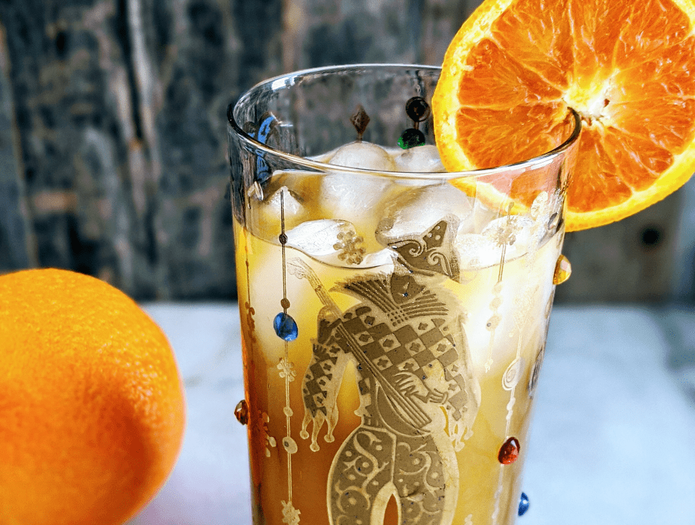 Close up of a Brass Monkey Cocktail in a mardis gras style glass garnished with an orange