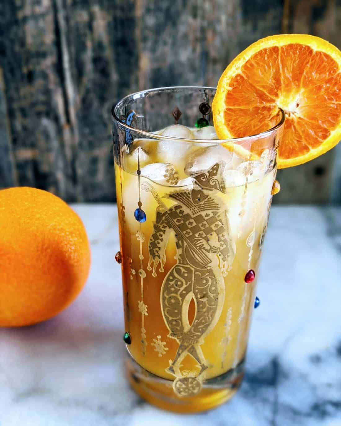 Vertical photo of a Brass Monkey Cocktail in a Mardis Gras style tumbler garnished with an orange. Whole orange in the background.