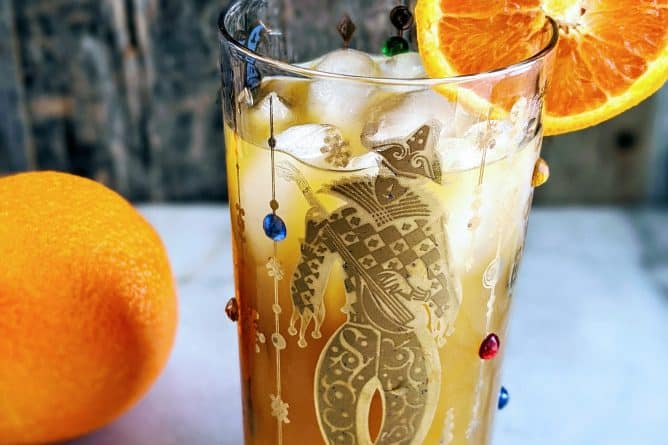 Vertical photo of a Brass Monkey Cocktail in a Mardis Gras style tumbler garnished with an orange. full orange in the background.
