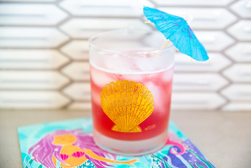 Bay Breeze cocktail in a glass emblazoned with a gold seashell garnished with a blue umbrella on a mermaid napkin.