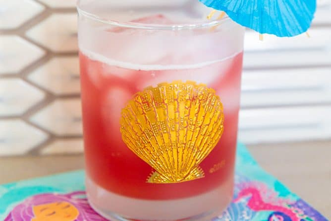 Bay Breeze Cocktail in a glass emblazoned with a gold shell and garnished with a small umbrella on a mermaid napkin