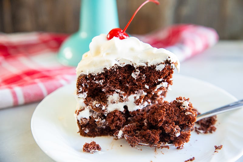 a slice of chocolate soda cake on a white plate with a piece of red cherry on top