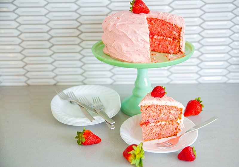strawberry cake on a jadeite cake stand with fresh strawberries, white plates and forks