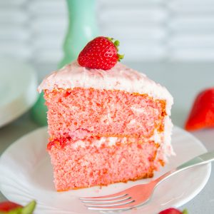 slice of strawberry cake on a white plate with a piece of fresh strawberry on top and a fork beside the plate