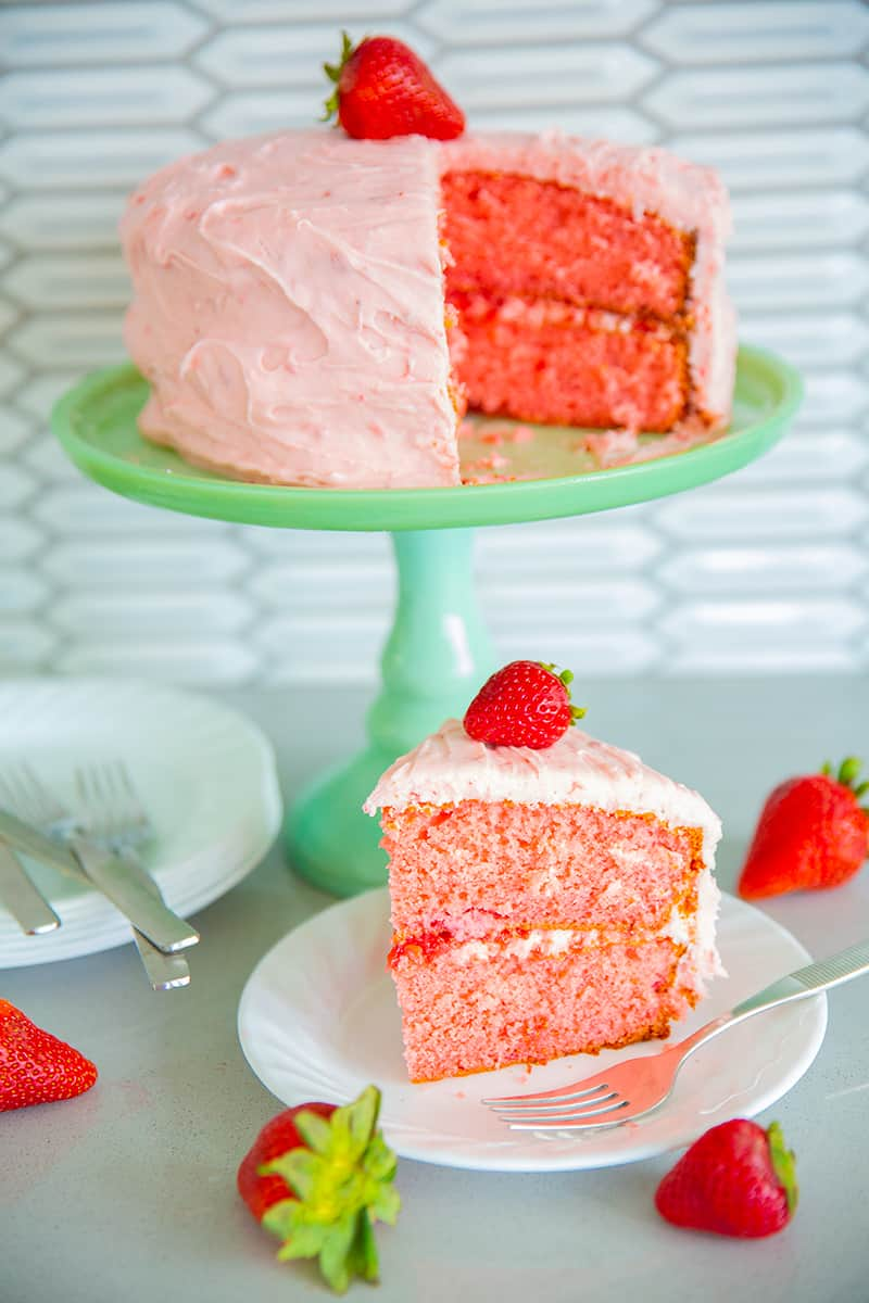 strawberry cake on a jadeite cake stand with strawberries, white plates and forks