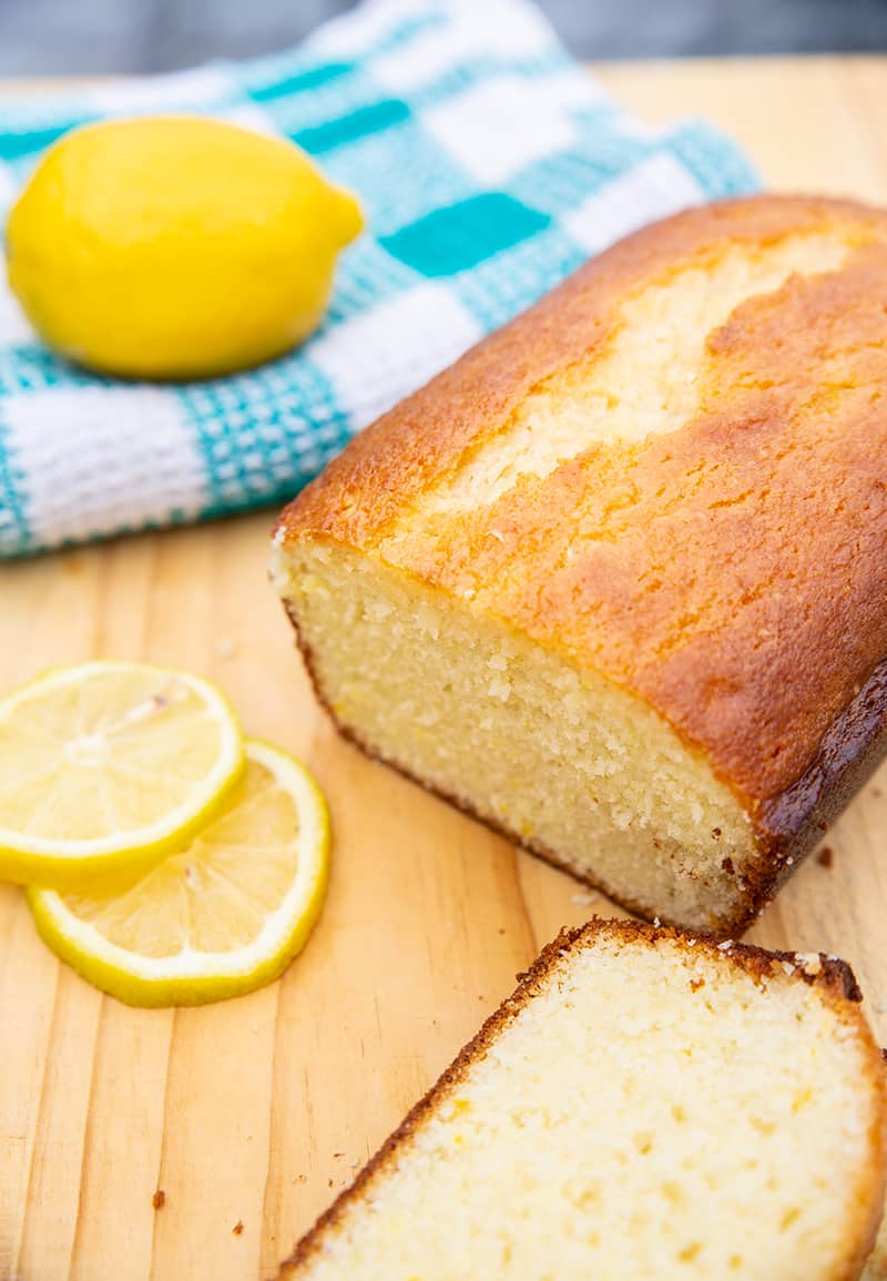 lemon bread sitting on a wooden board with lemons and a turquoise kitchen towel