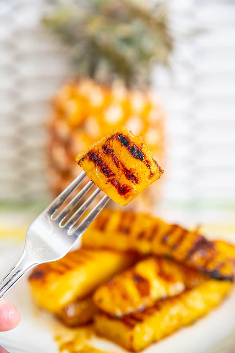 fork holding a piece of Grilled Pineapple slice
