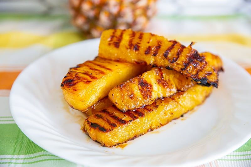 Grilled Pineapple slices on a while plate