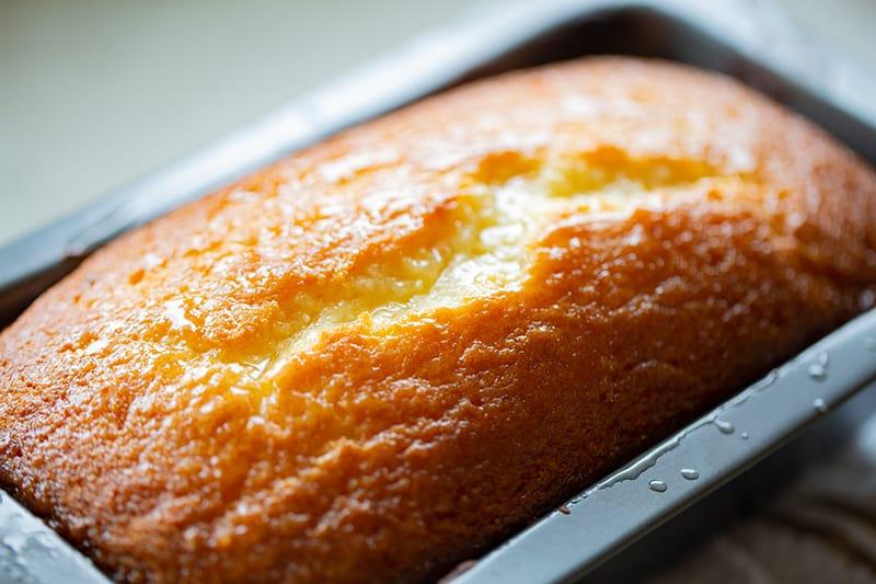 glazed lemon bread in an aluminum bread pan