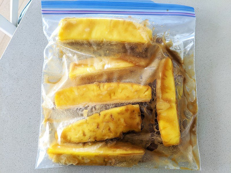 pineapple slices and marinade inside a large sealing plastic freezer bag