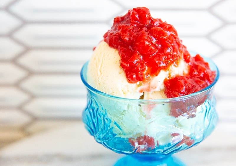 Strawberry compote on vanilla ice cream in a blue glass dish