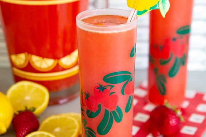 Strawberry Lemonade in two glasses and a pitcher with lemons and strawberries on a counter