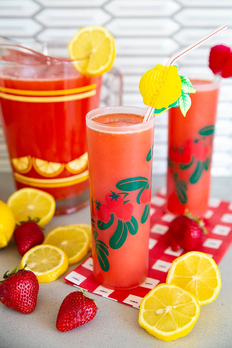 Strawberry Lemonade in tall glasses on a counter with lemons and strawberries - there is a pitcher in the background