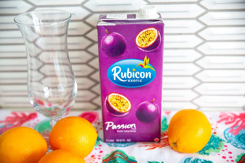 A container of passion fruit juice on a counter surrounded by oranges