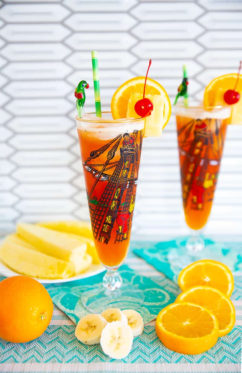 Rum Runner Cocktail in a tall pirate designed pilsner glass on a turquoise tablecloth surrounded by oranges, pineapple wedges and banana slices.