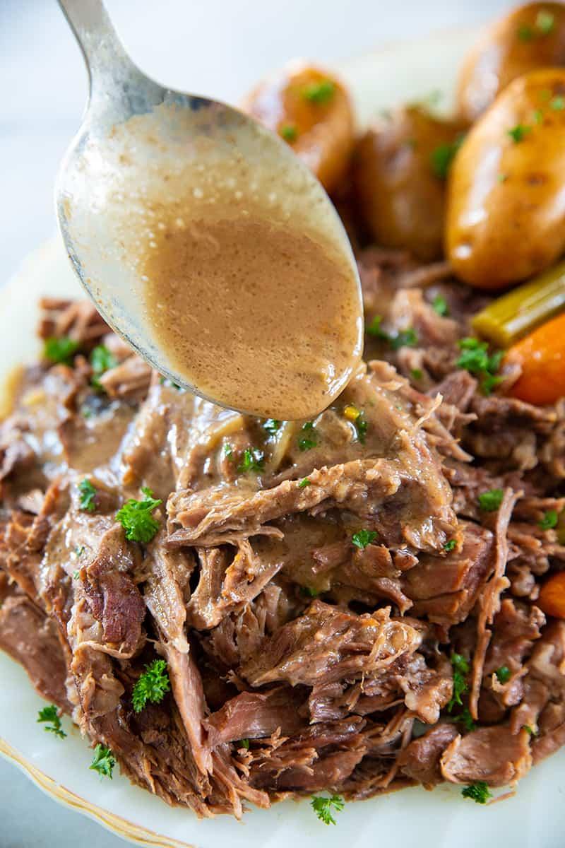 spooning gravy over pot roast
