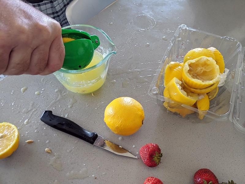 hand squeezing lemons for lemon juice