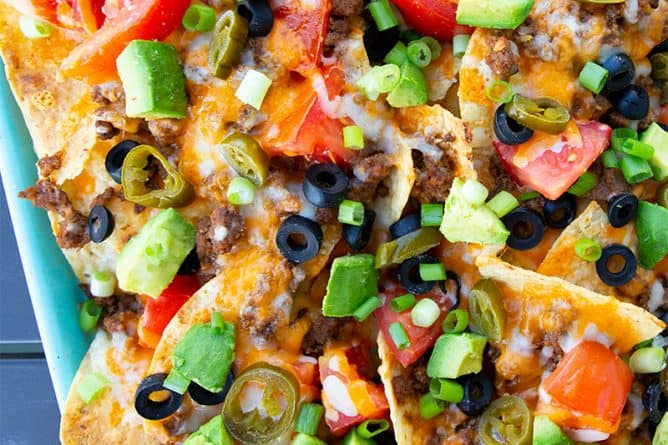 close up of Taco Sheet Pan Nachos on a turquoise cookie sheet