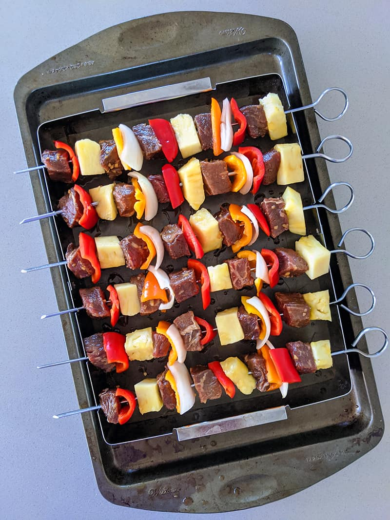 raw beef kabobs on a baking sheet