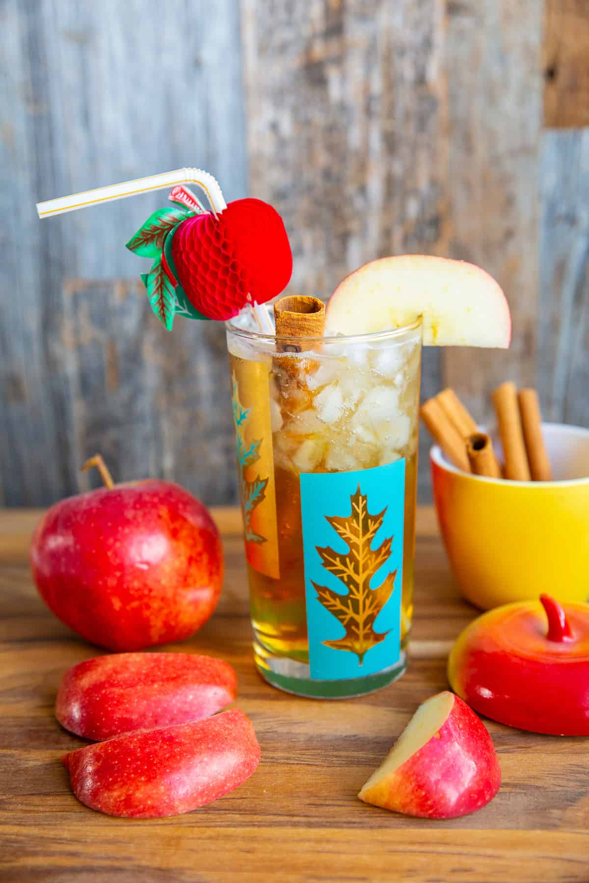 Apple Cider Cocktail in a turquoise and gold glass on a wood board surrounded by cinnamon sticks and apples.