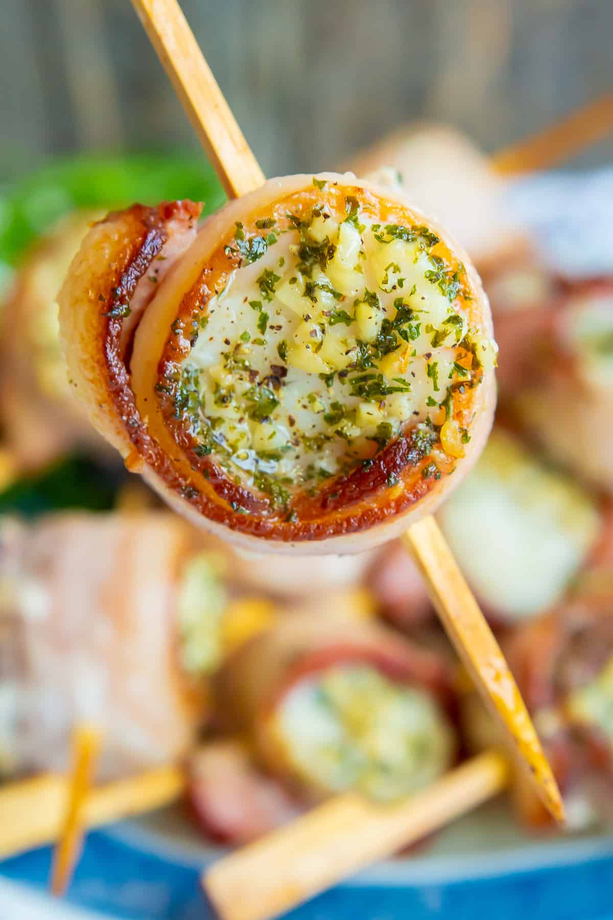 close up piece of Bacon Wrapped Scallops in a small bamboo skewer