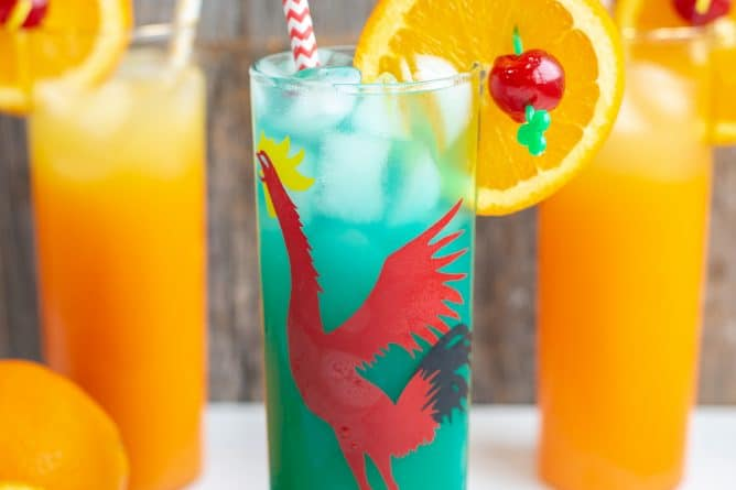 Green Screwdriver in a red rooster glass, garnished with orange slice and cherry