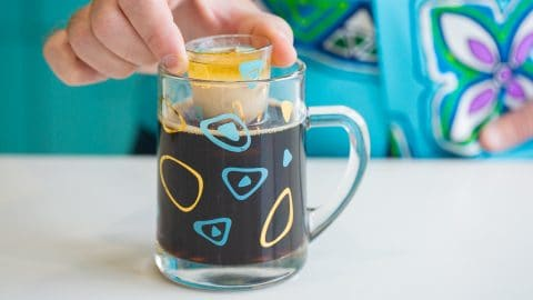 Close up of shot glass filled with irish cream and irish whiskey held over a mug full of beer